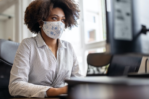 Woman working on a computer with a mask